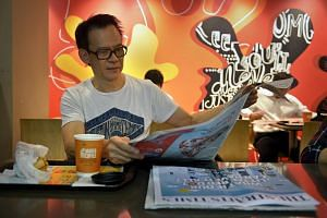 Chauffeur, Mark Yow, 55, reading a copy of the newly relaunched Straits Times in the McDonald's at Clifford Centre.