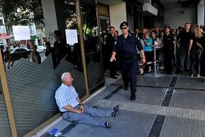 Retiree Giorgos Chatzifotiadis seen crying outside a national bank branch as pensioners queue to get their pensions, with a limit of 120 euros, in Thessaloniki on July 3, 2015.