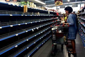 Shoppers stand in an aisle with empty shelves in a supermarket in Athens on July 4, 2015.