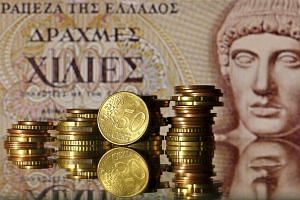 Euro coins are seen in front of an old 1,000-drachma note which shows the head of Apollo.