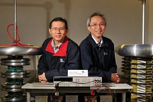 Dr Chua Sze Wey (right) and research engineer Lim Kuan Hoong with the setup to demonstrate the measurement of electrical current generated in a human body.