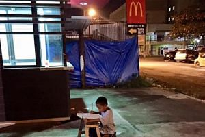 A picture of a boy doing his homework by a roadside in the Philippines has gone viral.