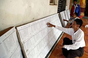 People checking voter lists in Rakhine state in Myanmar. The Nov 8 poll will open a new chapter for Myanmar, which is still fragile and making a transition from decades of military rule.