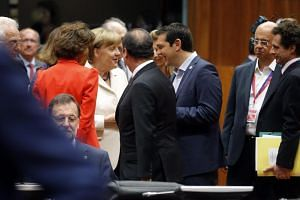 Greek PM Alexis Tsipras (third from right) speaking to German Chancellor Angela Merkel and French President Francois Hollande at the start of the summit.