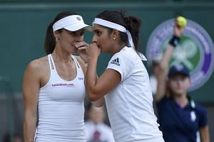 Hingis and Mirza (right) talk during the women's doubles final at Wimbledon.