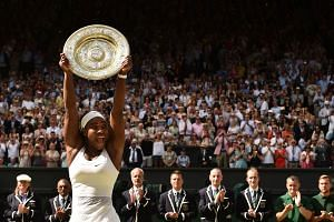 Serena Williams celebrates with the winner's trophy, the Venus Rosewater Dish, after her women's singles final victory over Spain's Garbine Muguruza at the 2015 Wimbledon Championships.