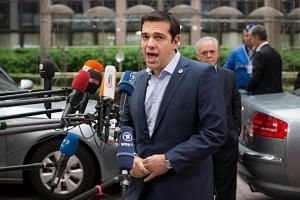 Greek PM Alexis Tsipras speaking to the media as he arrives for the Brussels summit.