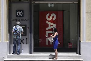 A woman waits to withdraw some money at an ATM in Athens on July 13, 2015.