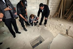 Mexico's Attorney General Arely Gomez Gonzalez (second from right) looks into the entrance of a tunnel connected to the Altiplano Federal Penitentiary and used by drug lord Joaquin 'El Chapo' Guzman to escape.