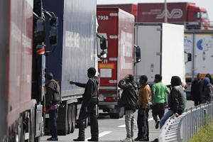A group of migrants gather near a line of lorries waiting on the motorway which leads to the Channel Tunnel terminal in Calais, northern France, on June 24, 2015.