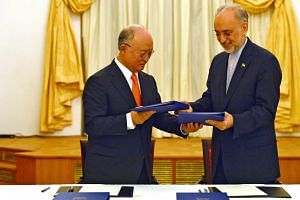 IAEA Director General Yukiya Amano (left) and Vice President of the Islamic Republic of Iran Ali Akhbar Salehi signing a roadmap for the clarification of past and present issues regarding Iran's nuclear program in Vienna July 14, 2015.