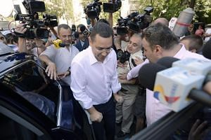 Romanian PM Victor Ponta leaving the National Anti-Corruption Bureau (DNA) headquarters on crutches.