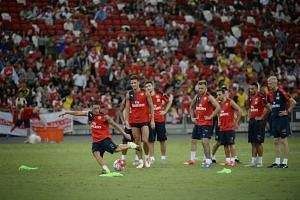Arsenal's Mesut Ozil (left) takes a kick as teammates and manager Arsene Wenger (far right) look on at the National Stadium during a training session on July 14.