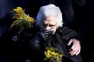 A relative of an Australian victim of Malaysia Airlines jet MH17 reacts before placing a floral tribute at a memorial that was unveiled outside Parliament House in Canberra, Australia, on July 17, 2015.