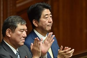 Japan's Prime Minister Shinzo Abe (right) and Regional Revitalization Minister Shigeru Ishiba (left) react after passing controversial security bills in Tokyo on July 16, 2015.