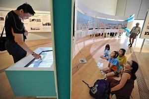 Visitors viewing interactive displays at the Home gallery of the Singapore STories: Then, Now, Tomorrow exhibition at the ArtScience Museum. The exhibition has six galleries, in themes matching the newspaper's sections: Business, Home, World, Sport,