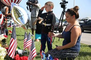 Blake Miller and his mother, Ashley Miller whose husband is a Lieutenant in the Marine Corps pay their respects to those killed in the shooting on July 17, 2015 in Chattanooga, Tennessee.