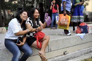 Domestic helpers using mobile phones near City Plaza.