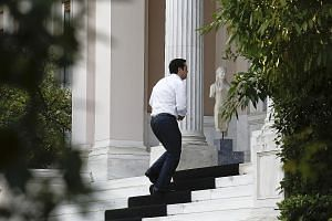Mr Alexis Tsipras arriving at Maximos Mansion, the official seat of the Prime Minister in Athens, last Wednesday, before 229 Greek lawmakers voted in favour of measures demanded by Greece's creditors as a condition for further aid, with 64 voting aga