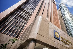 Signage for the Monetary Authority of Singapore (MAS) is displayed outside the central bank's headquarters in Singapore.