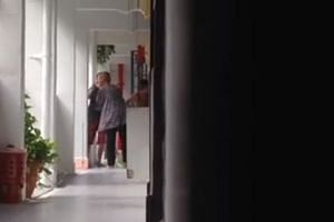 The elderly woman receiving a slap from one of the two watching women outside a HDB flat at Lower Delta Road.