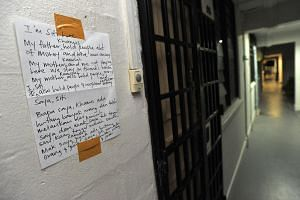 A note outside the flat of elderly woman Kamisah Burel, 58, who was abused by her daugher.