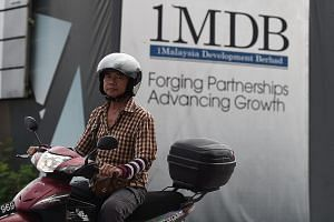 A motorcyclist rides past hoarding at the construction site of 1MDB's flagship Tun Razak Exchange in Kuala Lumpur.