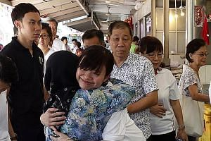 Ms Tin Pei Ling (white top) being hugged by MacPherson resident, Madam Fatimah Buang, 75, during her visit to a market yesterday.