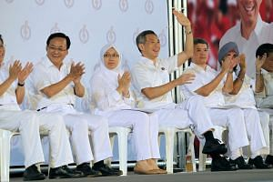 PM Lee Hsien Loong (waving) with his six-member Ang Mo Kio GRC team at a PAP rally during the 2011 general election.