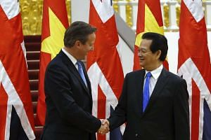 British PM David Cameron (left) poses for a photo with Vietnamese counterpart Nguyen Tan Dung in Hanoi.