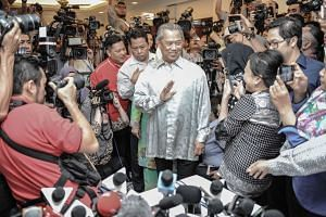 Muhyiddin Yassin (centre) waves to journalists as he arrives before a press conference at his residence in Kuala Lumpur on July 29, 2015.