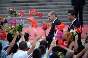 Turkish President Recep Tayyip Erdogan (left), accompanied by Chinese leader Xi Jinping, being welcomed by a group of children in Beijing yesterday. Mr Xi stressed that Mr Erdogan's three visits to China as both premier and president showed he was at