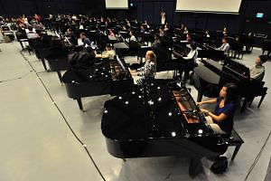 More than 90 musicians from the Metropolitan Festival Orchestra and the Sing50 orchestra mentees, alongside 50 pianists and Sing50 band rehearsing for Sing50 concert on 26 July 2015. PHOTO: LIM YAOHUI