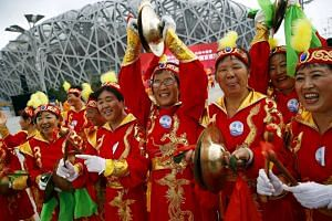 Performers cheer ahead of IOC's announcement of the winner city for the 2022 winter Olympics bid on July 31, 2015.