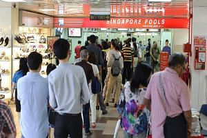 Punters queueing to place bets at a Singapore Pools outlet. A spokesman for the lottery operator said that they would have to study offering self-service kiosks in more detail to see if customers used to counter service for years would be receptive t