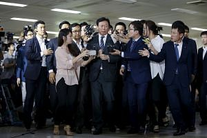 Shin Dong Bin (centre), Lotte Group chairman and the younger son of Lotte founder Shin Kyuk Ho, is surrounded by the media as he makes his way upon his arrival at Gimpo Airport in Seoul, South Korea.