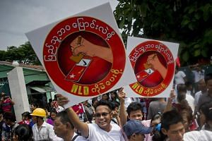 National League for Democracy supporters hold up posters in support of National League for Democracy chairperson Aung San Suu Kyi (not pictured) in Yangon on July 29, 2015.