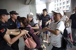 Relatives of passengers push policemen as they try to enter the building where the Malaysia Airlines office is located in Beijing on Aug 5, 2015.