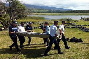 Police carrying the washed-up debris on Reunion island on July 29, 2015.