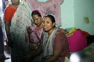 The wife (right) of murdered Bangladeshi blogger Niloy Chakrabarti, who was known for his atheist views in the Muslim- majority country, weeping at their home in Dhaka yesterday.
