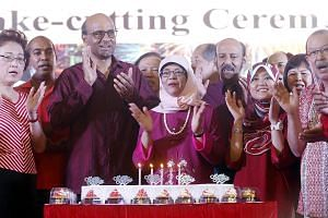 Deputy Prime Minister Tharman Shanmugaratnam (third from left), Madam Halimah Yacob (centre), and Madam Rahayu Mahzam (third from right) attended a National Day dinner in Bukit Batok yesterday. Madam Rahayu will replace Madam Halimah in Jurong GRC.
