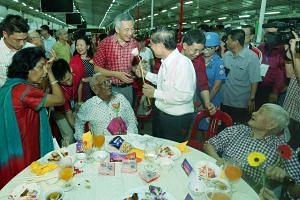 Prime Minister Lee Hsien Loong and Minister for Transport Lui Tuck Yew present flowers to pioneers during the National Day Dinner on Aug 8, 2015.