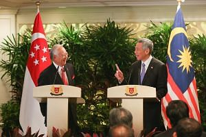Malaysian PM Najib Razak (left) and Prime Minister Lee Hsien Loong speaking to the media at their annual leaders' retreat at Shangri-La Hotel on May 5, 2015.