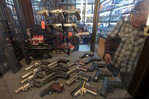 This photo taken on July 22, 2015 shows a Thai man walking past handguns displayed at a gun shop in Bangkok.