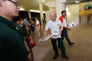 DPP secretary-general Benjamin Pwee distributing fliers at Bishan MRT station. Behind him is SPP central executive committee member Kumar Appavoo. The parties are joining forces to contest Bishan-Toa Payoh.