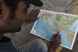 A Syrian migrant looking at a map of Europe as he plans the next part of his trip to Central Europe in the Kara Tepe migrant camp on Lesbos on Aug 13, 2015.