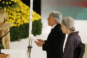 Japan's Emperor Akihito delivers a speech next to Empress Michiko after they offer a moment of silence to the war dead during a memorial service marking the 70th anniversary of Japan's surrender in World War Two at Budokan Hall in Tokyo on August 15,