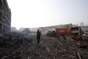 A firefighter films the aftermath next to a damaged firefighting vehicle at the site of Wednesday night's explosions in Binhai new district of Tianjin, China, on Aug 15, 2015.
