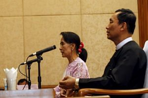 File photo of Myanmar pro-democracy leader Aung San Suu Kyi talking to the media as Shwe Man, Speaker of the Union Parliament, sits beside her during their joint news conference at Parliament in Nyapyitaw.