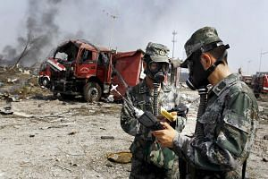 Soldiers of the People's Liberation Army anti-chemical warfare corps work next to a damaged firefighting vehicle at the site of Wednesday night's explosions at Binhai new district in Tianjin, China on Aug 16, 2015.